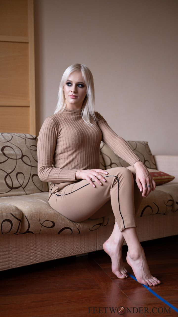 Feet model sits on the sofa