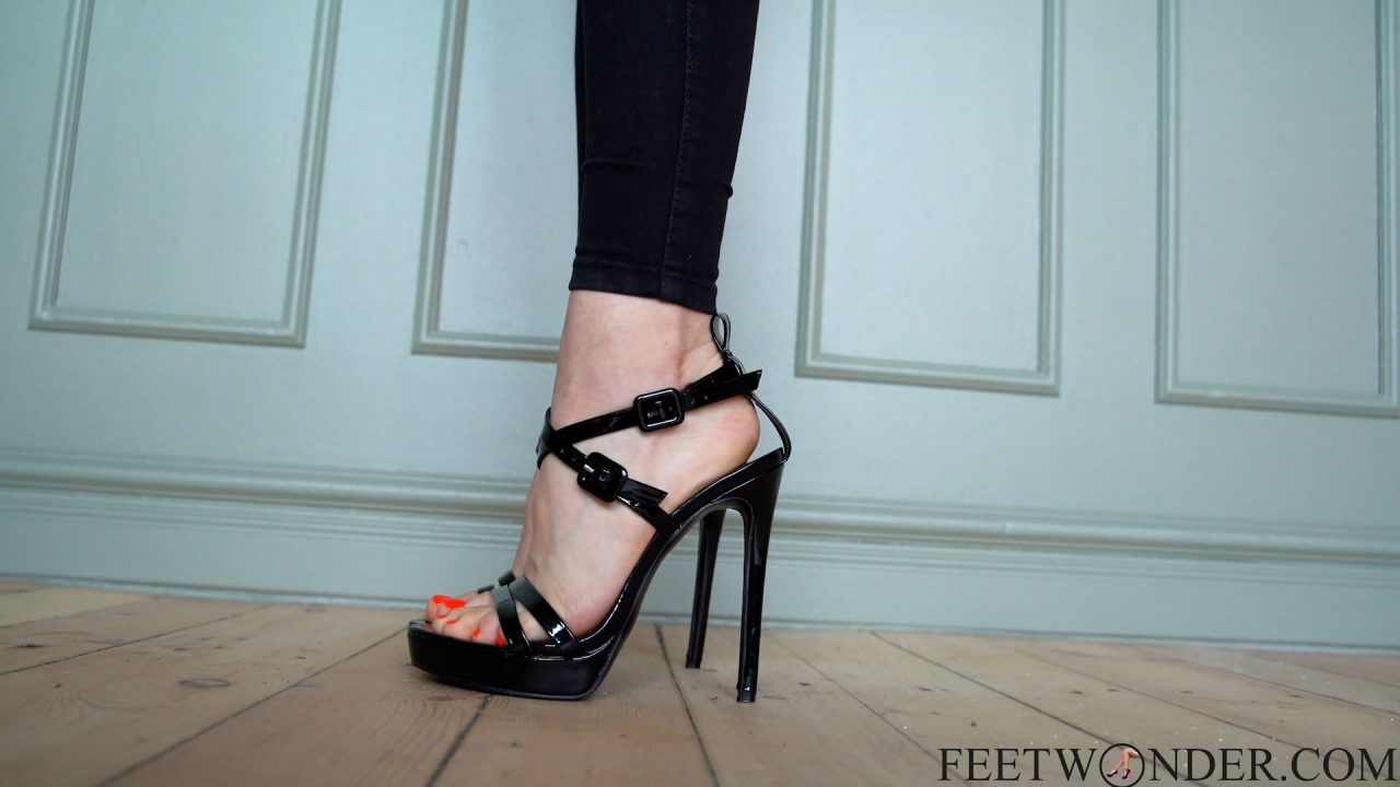 Female feet with red toes in high heels