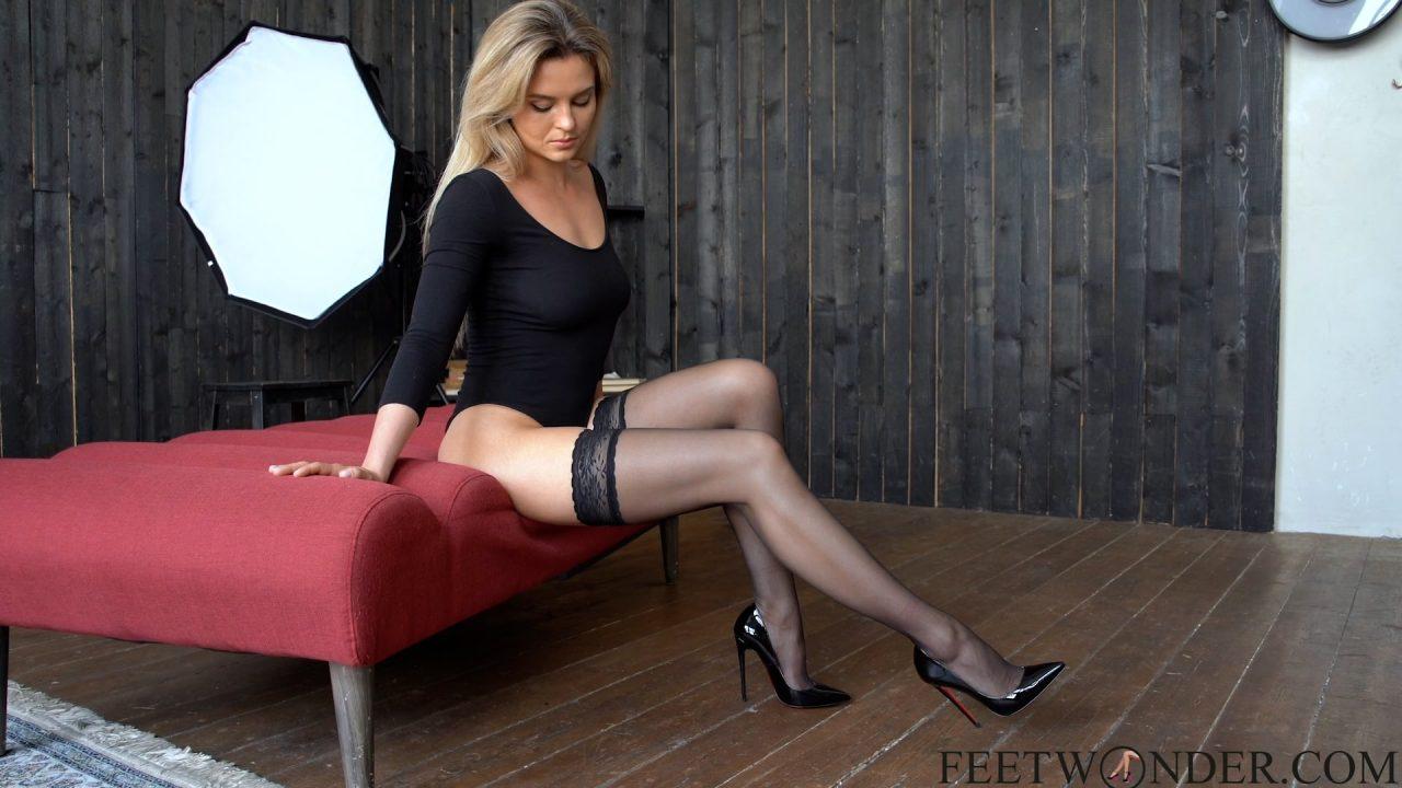 beautiful feet model poses in black nylon stockings
